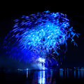 Celebratory blue firework in a night sky Stock Photo