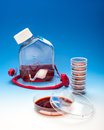 Cell culture or bacterial experiment tools and safety glasses on blue gradient background Royalty Free Stock Photos