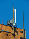 Cell phone antenna, transmitter. Telecom radio mobile antenna against blue sky Royalty Free Stock Photo