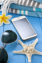 A cell phone with a blank screen in a tropical vacation setting with a seaside theme Stock Photography