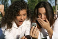 Cell phone shocked teens Royalty Free Stock Image