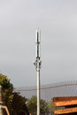 Cell phone tower against an overcast sky with rusting steel in the foreground Stock Image
