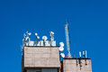 Cellular antenna on the roof of the building against the blue sky Royalty Free Stock Image