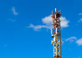 Cellular connection tower with transmitters and antennas over a blue sky background Stock Photo