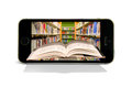 Cellular smart phone books reading online library book coming out of a with a in the background representing and at with Stock Image