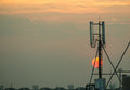 Cellular tower against sunset in background Royalty Free Stock Photo