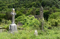Celtic cross overgrown graveyard next to medieval church st kevin monastic heritage site glendalough south dublin ireland Royalty Free Stock Photos