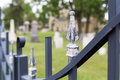 Cemetary gate selective focus on the fence of a grave yard can be seen in soft focus behind it in the background Stock Photography