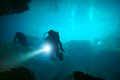 Cenote underwater divers in with torchlight Royalty Free Stock Photos