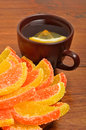 Ceramic brown cup with tea and candied fruit on the brown board Stock Photo