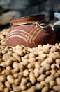 Ceramic hand made jug foreground peanuts inside jug as hinted smoke there s anti insect insence Stock Photography