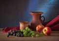 Ceramic jug, grapes and peaches Stock Photos