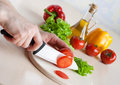 Ceramic knife in hand cutting tomatoes for salad Royalty Free Stock Photography