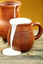 Ceramic mug with cream and clay jug. Royalty Free Stock Images