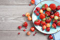 Ceramic plate with fresh summer berries  at old wooden table. Royalty Free Stock Photo