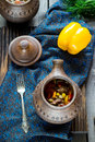 Ceramic pot with meat and vegetables,yellow pepper and napkin on dark wooden table. Royalty Free Stock Photo