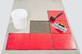 Ceramic tilles and tile adhesive on floor bucket rubber hammer trowel Stock Photo