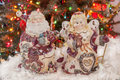 Ceramic toy of santa clause and mrs clause on white decor like a snow is as a christmas candle decoration behind them is christmas Royalty Free Stock Photo
