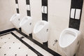 Ceramic urinal four in a men toilet Stock Photography