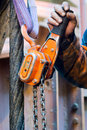Chain hoist with hand a bright orange attached next to a wire rope operating lever Royalty Free Stock Photo