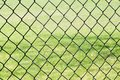 Chain link fence against grass black empty green field Royalty Free Stock Photography