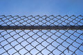 Chain link fence with bar against blue sky a a sturdy behind the mesh and fastenings a wispy clouds Royalty Free Stock Photos