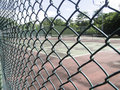 Chain Link Fence with tennis court background Royalty Free Stock Photo