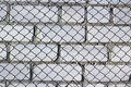 Chain link fence on white brick wall Royalty Free Stock Photo