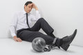 Chained businessman full length of depressed businessman sittin sitting on the floor with shackles to his legs Royalty Free Stock Image