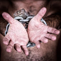 Chained hands asking for freedom gesturing to symbolize the need in a dark background Stock Images
