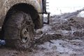 Chained up tire on a very muddy road trucks front with chains you can see in the distance and closeup of and chain Royalty Free Stock Images