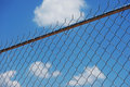 Chainlink fence against blue sky Royalty Free Stock Photo