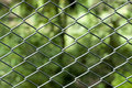 Chainlink fence with blurred green background Royalty Free Stock Photo