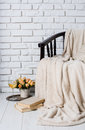 Chair with blanket old books flowers and wine on a white brick wall background room interior Royalty Free Stock Photography