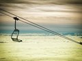 Chair lift sight on an empty and cable with cloudy valley in the background Royalty Free Stock Photo