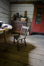 Chair in old rustic country rural farm kitchen a log cabin a lone is the focal point of this quaint image from a historical site Stock Images