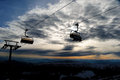 Chair ski lift skiers silhouette in over clouded sky and mountains at sunset Royalty Free Stock Photography