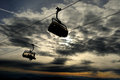 Chair ski lift skiers silhouette in over clouded sky at sunset Royalty Free Stock Images