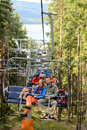Chairlift going through forest with young people Stock Image