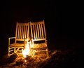 Chairs afire white rocking with flames during the night Royalty Free Stock Photos