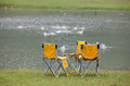 Chairs on lake side Royalty Free Stock Photo