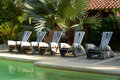 Chairs at resort in tropical location pool Royalty Free Stock Photo
