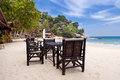 Chairs and table on the sand beach with blue sky Stock Images