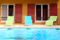 Chaise longue near the open air swimming pool Stock Photos