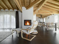 Chaise longue near to fireplace in a living room foreground of the overlooking on dining with wood ceiling Stock Photo