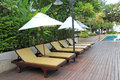 Chaise longue at the poolside in thailand Stock Photos