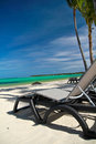 Chaise-longues on caribbean sea beach Royalty Free Stock Images