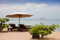 Chaise lounges and umbrella on an ocean coast. Stock Photos