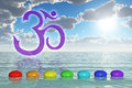 Chakra stones on the sea d rendering of a om symbol and with rainbow colors Royalty Free Stock Photo