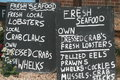 Chalk board signs advertising fish for sale